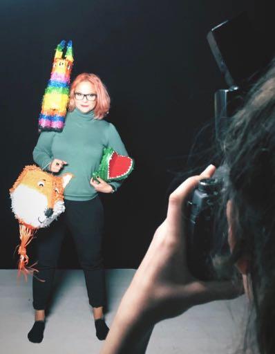 Karin står i studion med tre stycken pinatas. I förgrunden syns fotografen Olivia Eriksson som fotar Karin.